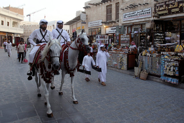 Qatari men ride horses as they parade at Souq Waqif market in Doha, Qatar August 30, 2016. (Photo by Naseem Zeitoon/Reuters)
