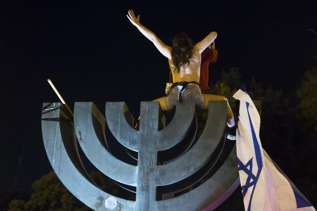 A woman sits on the Israeli national emblem during a demonstration on July 21, 2020 in Jerusalem, Israel. Demonstrations continue against Prime Minister Benjamin Netanyahu and the government's handling of the coronavirus (COVID-19) crisis. (Photo by Amir Levy/Getty Images)