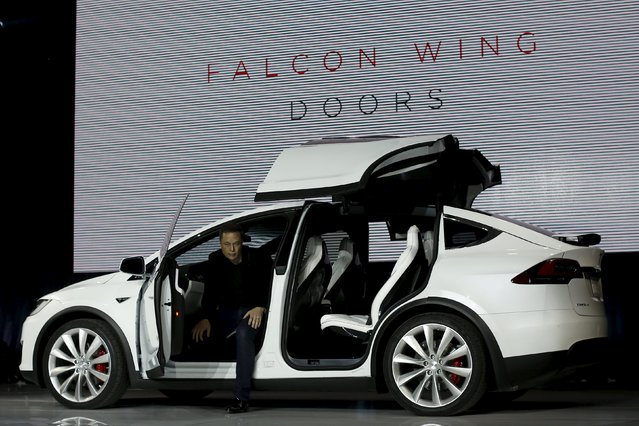 Tesla Motors CEO Elon Musk introduces the falcon wing door on the Model X electric sports-utility vehicles during a presentation in Fremont, California September 29, 2015. Tesla Motors delivered the first of its long-awaited Model X electric sports-utility vehicles on Tuesday, a product investors are counting on to make the pioneering company profitable after years of losses. (Photo by Stephen Lam/Reuters)