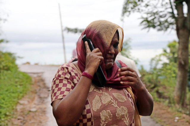 A Sri Lankan landslide affected woman cries speaking on a mobile telephone as she hurries towards safety at Meeriyabedda, Haldummulla in Badulla 218 kms towards the interior from Colombo, Sri Lanka, 29 October 2014. At least 14 people were killed in a landslide in central Sri Lanka and a search operation was launched for some 250 villagers reported missing, an official said and the army, air force and police are involved in the search operation. (Photo by M. A. Pushpa Kumara/EPA)