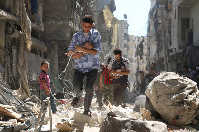 Syrian men carrying babies make their way through the rubble of destroyed buildings following a reported air strike on the rebel-held Salihin neighbourhood of the northern city of Aleppo, on September 11, 2016. Air strikes have killed dozens in rebel-held parts of Syria as the opposition considers whether to join a US-Russia truce deal due to take effect on September 12. (Photo by Ameer Alhalbi/AFP Photo)
