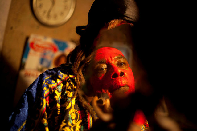 In this January 27, 2013 photo, snake handler Saintilus Resilus looks in the mirror as he paints his face red before performing with snakes for money during the pre-Lenten Carnival season at his home in Petionville, Haiti. It's the serpents that help him eat and pay rent, in addition to his work for a neighborhood herbologist. And it's the snakes for which he's most famous. (Photo by Dieu Nalio Chery/AP Photo/Matt Dayhoff)