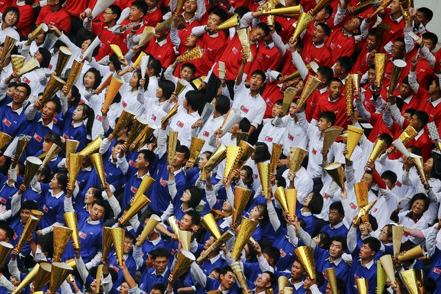 North Korean fans in national colours cheer during their team's preliminary 2018 World Cup and 2019 AFC Asian Cup qualifying soccer match against Philippines at the Kim Il Sung Stadium in Pyongyang October 8, 2015. (Photo by Damir Sagolj/Reuters)