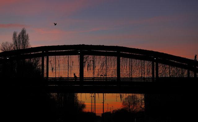 """A man runs along a bridge at sunset, at the """"Parco Nord"""" North Park in Milan, Italy, Monday, November 27, 2017. (Photo by Antonio Calanni/AP Photo)"""