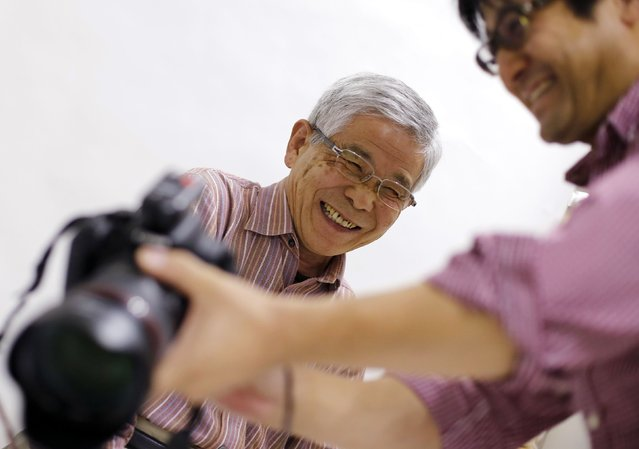 Kazuo Furumoto (L) reacts as he is shown his portrait that will be displayed at his funeral during an end-of-life seminar held by Japan's largest retailer Aeon Co in Tokyo October 24, 2014. (Photo by Toru Hanai/Reuters)