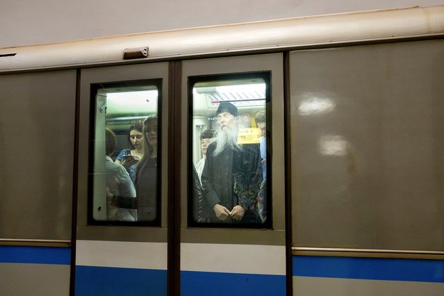 A priest seen through the window of a train. (Photo by Didier Bizet/The Washington Post)