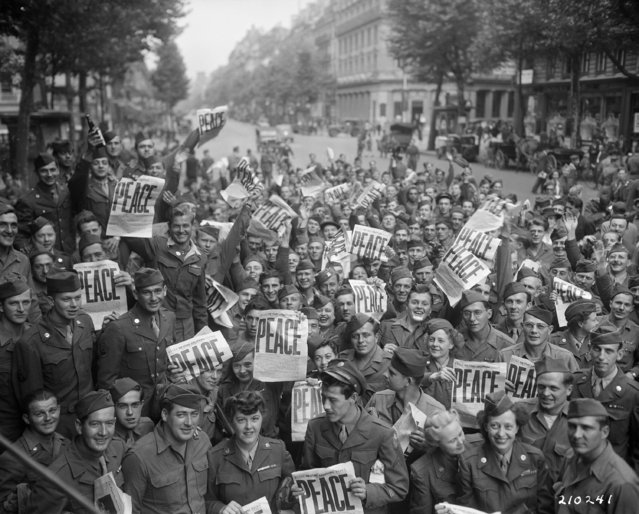"""American servicemen and women gather in front of ""Rainbow Corner"". Red Cross club in Paris to celebrate the unconditional surrender of the Japanese"". (Photo by an unknown photographer)"