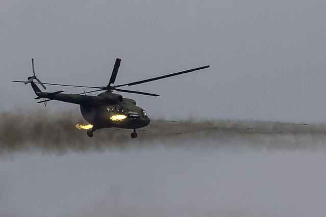 A Serbian Mi-8 helicopter gunship fires unguided rockets on targets during a training exercise in the village of Nikinci, west from Belgrade, November 14, 2014. Russian soldiers parachuted into open fields in western Serbia on Friday as part of an unprecedented joint military drill that has stirred controversy in the European Union candidate-country given the West-Russia standoff over Ukraine. (Photo by Marko Djurica/Reuters)