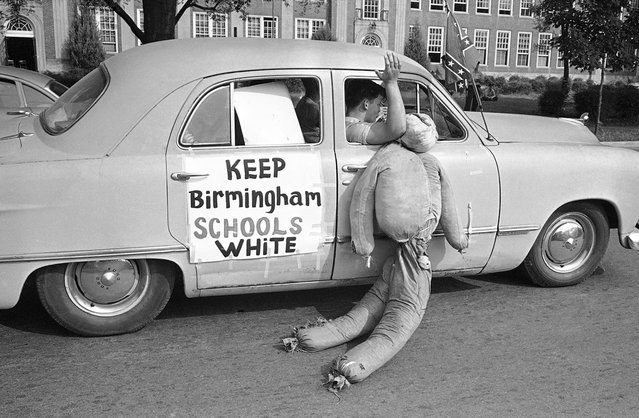 White students in Birmingham, Alabama, drag an African American effigy past West End High School, on September 12, 1963. Two African American girls attended the desegregated school and a majority of the white students were staying away from classes. Police stopped this car in a segregationist caravan in front of the school to caution them about fast driving and blowing auto horns in front of a school. (Photo by AP Photo)
