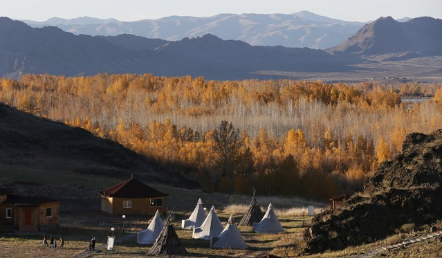 People visit an ethno-cultural complex in the Aldyn Bulak area during sunset on the bank of the Yenisei River outside the village of Ust-Elegest in Tuva region, Southern Siberia, Russia, October 7, 2015. (Photo by Ilya Naymushin/Reuters)
