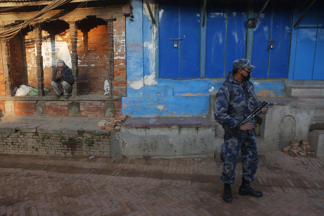 A Nepalese policeman stands guard as a man waits outside a polling station to cast his vote during the legislative elections in Thimi, Bhaktapur, Nepal, Thursday, December 7, 2017. (Photo by Niranjan Shrestha/AP Photo)