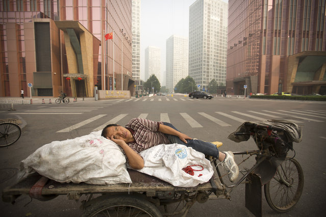 A man takes a nap on the back of his cart on a polluted day in Beijing, Tuesday, October 6, 2015. Air quality readings in the city on Tuesday were at levels considered hazardous by international measuring standards. (Photo by Mark Schiefelbein/AP Photo)