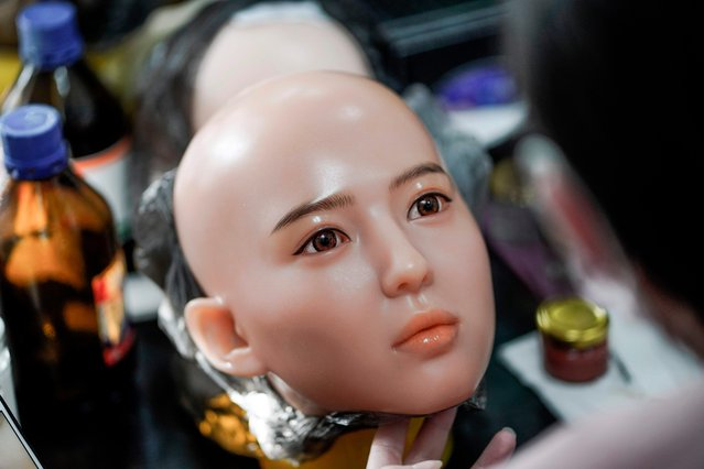 This photo taken on February 1, 2018 shows a worker painting the face of a silicone doll at a factory of EXDOLL, a firm based in the northeastern Chinese port city of Dalian. (Photo by Fred Dufour/AFP Photo)