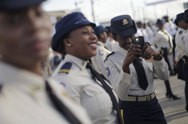 A national police officer takes a picture before the commemoration of the 209th anniversary of the killing of Jean-Jacques Dessalines in Port-au-Prince, Haiti, October 17, 2015. Dessalines was a leader of the Haitian Revolution against France and is considered a national hero. (Photo by Andres Martinez Casares/Reuters)