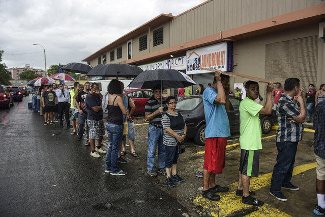 People wait in line to buy ice during a massive blackout in San Juan, Puerto Rico, Thursday, September 22, 2016. Repair crews work to restore electricity to Puerto Rico's 3.5 million people after a power plant fire blacked out the entire U.S. territory. The outage was the latest hit for an island mired in a decade-long economic crisis and whose government has warned it is running out of money as it seeks to restructure nearly $70 billion in public debt. Many Puerto Ricans expressed doubts that power would be restored quickly, saying the economic slump has affected basic government services. Hundreds of people took to social media to criticize the Electric Power Authority, noting that they already pay bills on average twice that of the U.S. mainland. (Photo by Carlos Giusti/AP Photo)