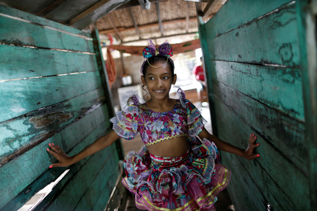"A member of the ""Bloco Real Folia"" group smiles inside her house during Carnival of the Waters, where costumed and colorful boats navigate the river Jaituba, around the islands near the city of Cameta, Brazil on February 8, 2018. (Photo by Ueslei Marcelino/Reuters)"