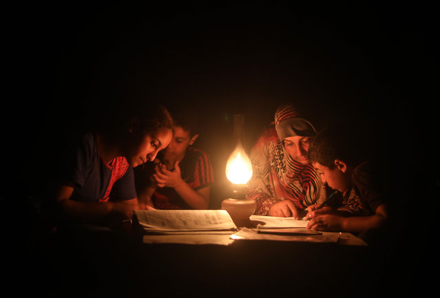 A woman helps children study under candle light during a power cut in Khan Yunis, Gaza on August 18, 2020. After Israel tightened the blockade in Gaza Strip, the only power plant in the area stopped production affecting the life especially the health sector. (Photo by Mustafa Hassona/Anadolu Agency via Getty Images)