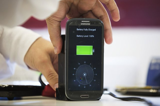 A lab worker disconnects from a charger a mobile phone, displaying a timer indicating that the battery was fully charged under 30 seconds, at the headquarters of StoreDot in Tel Aviv October 23, 2014. The Israeli company says it has developed technology that can charge a mobile phone in a few seconds and an electric car in minutes, advances that could transform two of the world's most dynamic consumer industries. (Photo by Finbarr O'Reilly/Reuters)