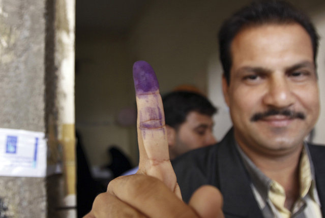 An Iraqi man holds up an ink-stained finger after casting his vote in the country's provincial elections in Basra, Iraq's second-largest city, on January 31, 2009. (Photo by Nabil al-Jurani/AP Photo/The Atlantic)