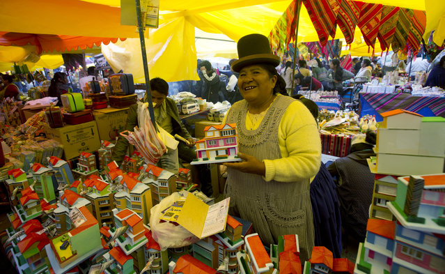 Vendor Maria Luisa sells miniatures homes at the annual Alasita fair in downtown La Paz, Bolivia, Wednesday, January 24. 2018. Thousands people attended the opening day of the fair to buy tiny replicas of things they aspire to acquire during the year, like homes, cars, wealth and love. (Photo by Juan Karita/AP Photo)