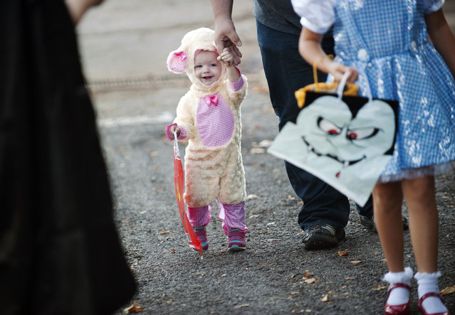 Laura Kienitz holds hands with her father Bobby Kienitz as they attend the Trunk or Treat at the Crown Health Services parking lot in Tyler, Texas on Thursday, October 29, 2015. Crown Health Services staff members decked out their cars with Halloween-inspired decorations and free candy for children. (Photo by Sarah A. Miller/Tyler Morning Telegraph via AP Photo)
