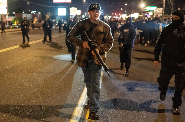 Patriot Prayer member Chandler Pappas carries an assault rifle while walking through a crowd of Black Lies Matter protesters on October 30, 2020 in Vancouver, Washington. Clark County Sheriffs deputies shot and killed Kevin E. Peterson, Jr., 21, Thursday night, sparking city-wide dueling protests between Black Lives Matter activists and supporters of President Donald Trump. (Photo by Nathan Howard/Getty Images)