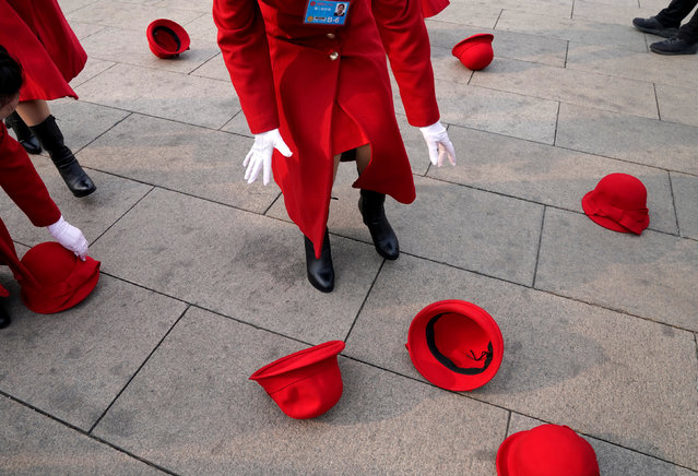 Hotel ushers pick up their hats after they threw to pose for a photo at Tiananmen Square as delegates attend the second plenary session of the National People's Congress (NPC) in Beijing on March 9, 2018. (Photo by Jason Lee/Reuters)