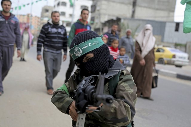 "A Palestinian boy wears green a headband with the Arabic, ""Ezz Al-Din Al Qassam brigade"", while holding a toy gun during a rally to commemorate the 27th anniversary of the Hamas militant group, at the main road in Jebaliya in the northern Gaza Strip, Friday, December 12, 2014. (Photo by Adel Hana/AP Photo)"
