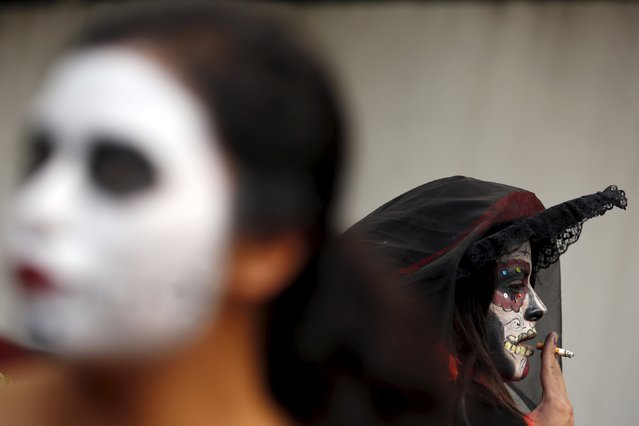 "A woman with her face painted to look like the popular Mexican figure called ""Catrina"", smokes a cigarette as she takes part in the annual Catrina Fest in Mexico City November 1, 2015. (Photo by Carlos Jasso/Reuters)"