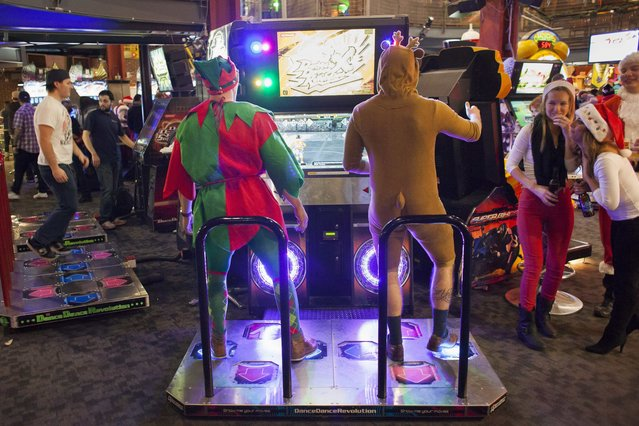 Santarchy participants play a dancing game at Gameworks in Seattle, Washington December 13, 2014. (Photo by David Ryder/Reuters)