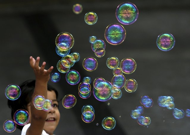 A migrant child plays with bubbles at Keleti railway station in Budapest, Hungary, September 6, 2015. (Photo by David W. Cerny/Reuters)
