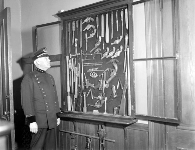Somerville police chief Thomas Damery with collection of murder weapons from 32 years of running down slayers, 1931. (Photo by Leslie Jones)