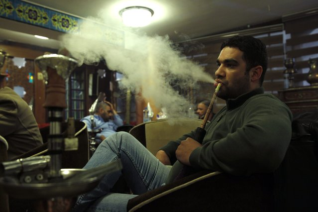 A man smokes shisha at a cafe in Baghdad December 17, 2014. (Photo by Thaier Al-Sudani/Reuters)