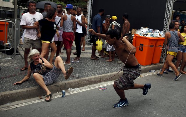 A man suspected of being a thief runs to escape from police officers during the LGBT Pride Parade in Copacabana beach in Rio de Janeiro, Brazil, November 15, 2015. (Photo by Pilar Olivares/Reuters)