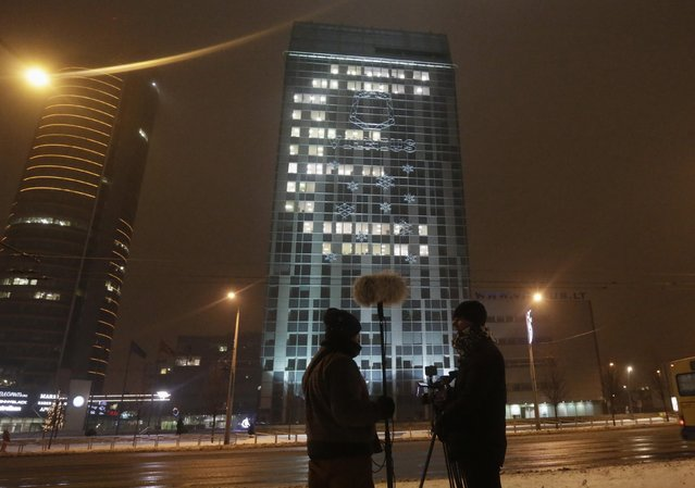 A television crew stands in front of the municipality building lighted up to form the Euro sign in Vilnius December 31, 2014. Lithuania will join euro zone on January 1, 2015. (Photo by Ints Kalnins/Reuters)