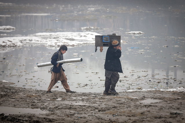 An Afghan father and son make their way towards home as they carry the stove to be used for heating in Kabul, Afghanistan, 24 November 2020. Due to the shortage of electricity, the majority of people in Afghanistan use coal and wood, as the only energy supply for warming their houses and cooking during the winter season. (Photo by Hedayatullah Amid/EPA/EFE)