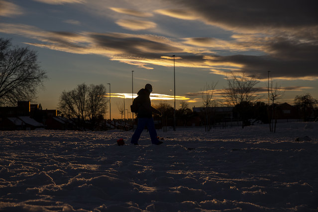 A man walks through the snow as the sunset in Rivas Vaciamadrid, Spain, Sunday, January 10, 2021. A large part of central Spain including the capital of Madrid are slowly clearing snow after the country's worst snowstorm in recent memory. (Photo by Manu Fernandez/AP Photo)