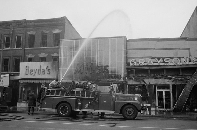 Firefighters spraying water on shops, including Beyda's, Miles Shoes, and Graysons, that were burned during the riots that followed the assassination of Martin Luther King, Jr., April 1968. (Photo by Reuters/Library of Congress)