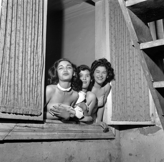 circa 1950:  Three prostitutes lean out of a window in Santiago, Chile, in an attempt to entice customers inside.  (Photo by Three Lions/Getty Images)