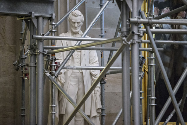A statue of President Abraham Lincoln stands amid scaffolding in the Capitol Rotunda on Capitol Hill in Washington, Wednesday, December 2, 2015, where extensive repairs continue on the cracks, leaks, and corrosion plaguing the cast-iron dome above. (Photo by J. Scott Applewhite/AP Photo)