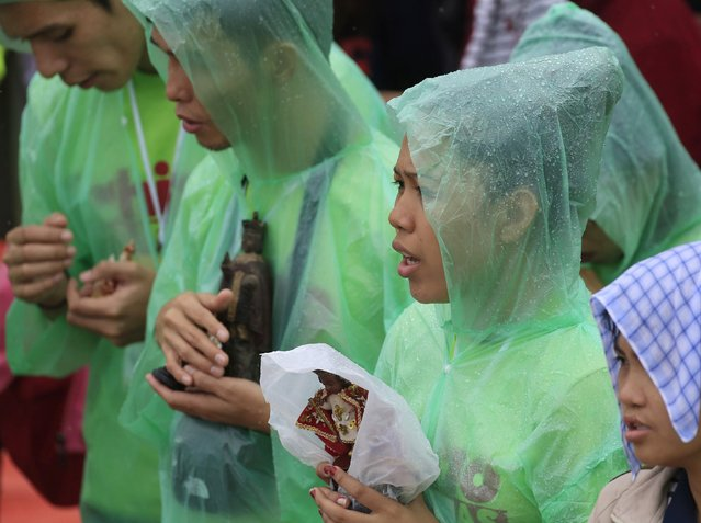 Pilgrims wear raincoats while holding statues of Baby Jesus during Pope Francis' meeting with youths at the University of  Santo Tomas (UST) in Manila January 18, 2015. (Photo by Romeo Ranoco/Reuters)