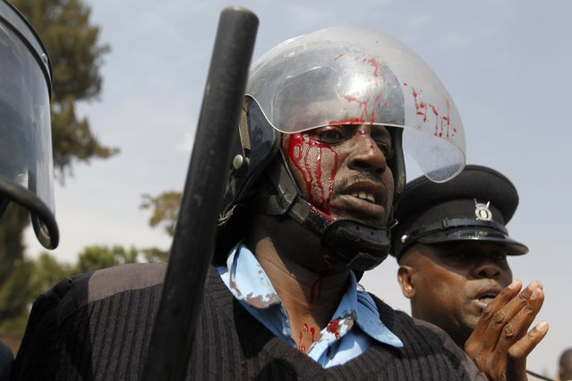 An injured riot policeman is seen during a protest by students of Langata primary school and activist against a perimeter wall erected by a private developer around their school playground in Kenya's capital Nairobi, January 19, 2015. (Photo by Thomas Mukoya/Reuters)