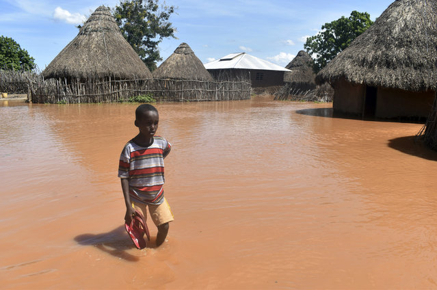 In this photo taken on Friday, April 27, 2018, a boy stands outside his family home, which has been submerged by floods following prolonged heavy rains in Tana Delta, Coastal Kenya. More than 30, 000 people in Tana River county have been displaced by floods which has also killed more than 5 people. (Photo by Andrew Kasuku/AP Photo)