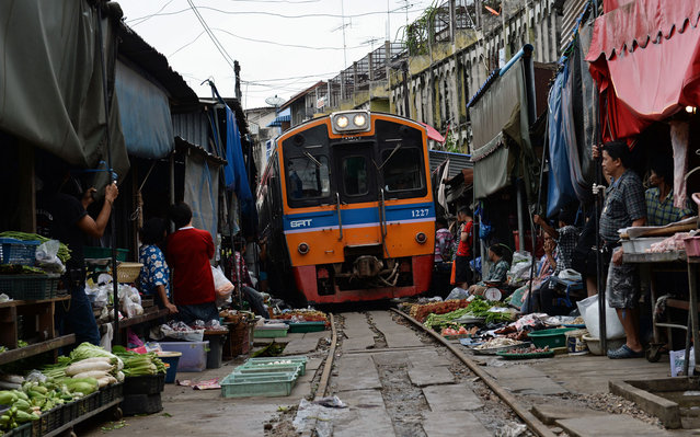 A train passes through a food market in Maeklong, some 60 kilometers south-west of Bangkok, on June 27, 2013. Several times a day, shopkeepers swiftly pack up their food stalls and pull back their canopies to let the trains pass. Once the trains have rumbled through, the crates of vegetables, fish and eggs, are heaved back into their position along the tracks and shoppers return to the tracks they use as a path through the market. (Photo by Christophe Archambault/Getty images)
