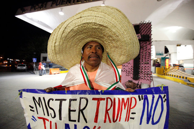 Martin Macias holds a placard against U.S. Republican presidential nominee Donald Trump while standing at Paso del Norte international border crossing bridge in Ciudad Juarez, Mexico, November 8, 2016. (Photo by Jose Luis Gonzalez/Reuters)