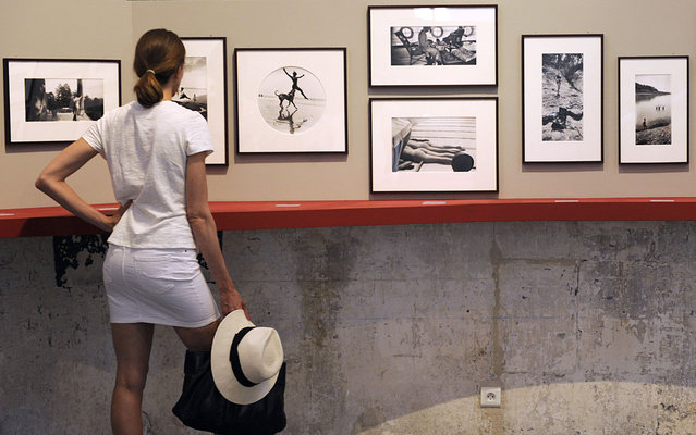 A visitor looks at pictures of French photographer Jacques-Henri Lartigue (1894-1986), on July 1, 2013 during the 44thd annual Rencontres d'Arles photography festival in Arles, southern France. The event runs until September 22. (Photo by Boris Horvat/AFP Photo)
