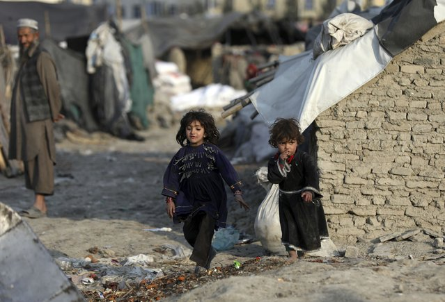 Internally displaced girls play outside their temporary home in the city of Kabul, Afghanistan, Monday, January 18, 2021. Half of war-ravaged Afghanistan's population is at risk of not having enough food to eat, including around 10 million children, Save the Children, a humanitarian organization said Tuesday. The group called for $3 billion in donations to pay for assistance in 2021. (Photo by Rahmat Gul/AP Photo)