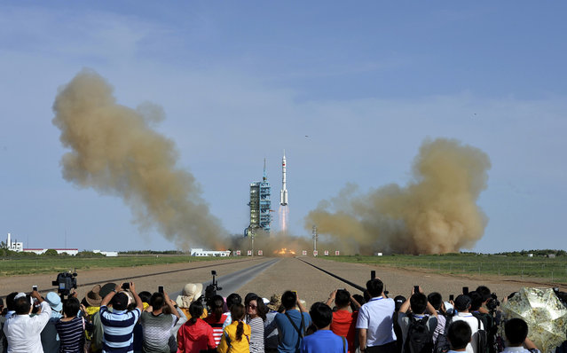 People observe the Long March 2-F rocket loaded with Shenzhou-10 manned spacecraft carrying Chinese astronauts Nie Haisheng, Zhang Xiaoguang and Wang Yaping lift off from the launch pad in the Jiuquan Satellite Launch Center, on June 11, 2013. (Photo by Reuters/Stringer via The Atlantic)