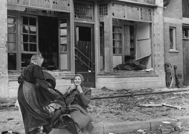 Two women with a pet kitten outside the ruins of their shop in the village of Wagenberg, Netherlands, November 1944. (Photo by Horace Abrahams/Keystone/Hulton Archive/Getty Images)
