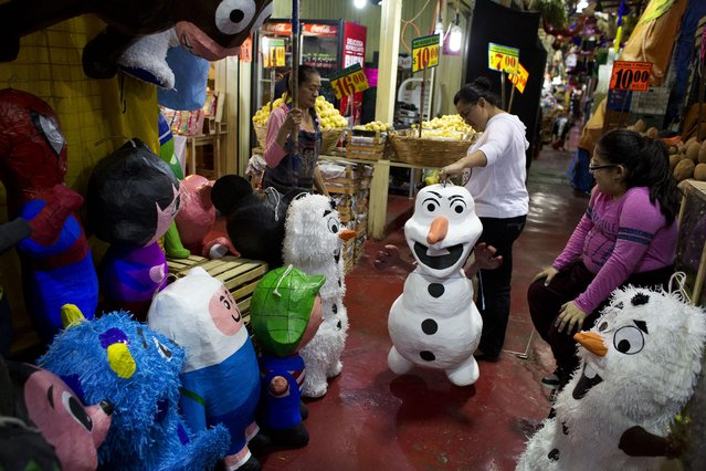 In this January 23, 2015 photo, Jasmin Membrillo, center, accompanied by her daughter Cinthya Jasmin, picks out a piñata representing Disney's Frozen snowman character Olaf, for an upcoming birthday party, at La Merced market in Mexico City. Market vendor Gerardo Moreno Alejo and his wife Edith, at left, sell piñatas and avocados from their stall in La Merced, one of Mexico City's largest markets. (Photo by Rebecca Blackwell/AP Photo)